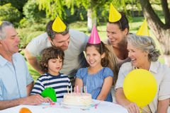 Extended family wearing party hats at birthday celebration in park Stock Photos