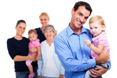 Extended family on white. Cheerful father holding his daughter with extended family on background Stock Images