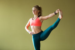 Extended Hand-To-Big-Toe pose. Portrait of sporty beautiful blond young woman in sportswear working out indoors, doing Utthita Hasta Padangustasana, Extended stock photo