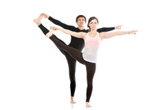 Extended Hand-To-Big-Toe yoga pose with partner. Two sporty people practice yoga with partner, couple doing stretching exercise, Extended Hand to Big Toe yoga stock photography