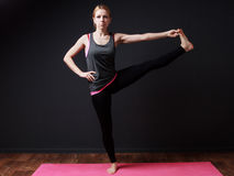 Extended hand to toe pose. Yoga. Young blonde woman doing yoga exercise royalty free stock images