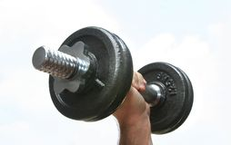 The extended hand with weight. The athlete has lifted the weight on a background of the sky Stock Images