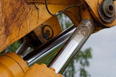 Extended piston rods. Close up of excavator hydraulic cylinders with extended piston rods Stock Photos