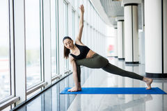 Extended Side Angle Pose. Young beautiful woman practicing yoga with panoramic windows in the background. Royalty Free Stock Image