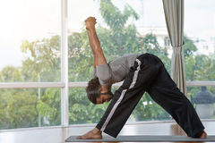 Extending triangle pose. Indian man practicing forward bending triangle pose Stock Photography