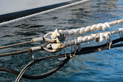 Extending white nautical ropes. Photo closeup of extending white nautical ropes seizing black marine cables metal fixing at seashore clear salt water reflecting Stock Photos