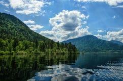 A extensão da água com a reflexão nubla-se entre as montanhas Nos bancos que crescem a floresta Imagem de Stock