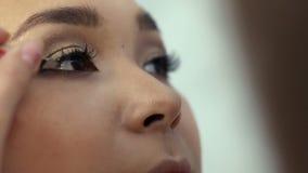 A extensão da pestana, maquilhador toma com chicotes artificiais do fórceps e da vara no olho da mulher video estoque