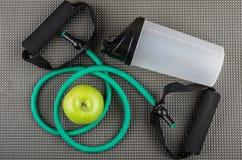 Extenseur tubulaire en caoutchouc, pomme verte et dispositif trembleur de plastique sur le tapis Images stock