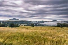 Extensión de campos verdes con los bosques montañosos fotos de archivo