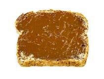 Extensión de la avellana del chocolate en la tostada del trigo integral aislada Fotos de archivo