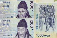 Extensión de los billetes de banco de la moneda a través del coreano del marco ganado fotografía de archivo