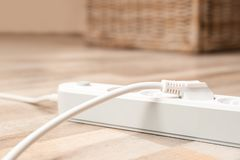 Extension cord on floor indoors, closeup. Electrician`s equipment royalty free stock photo