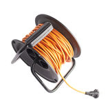 Extension cord on the reel. Orange extension cord on the black reel, composition isolated over the white background royalty free stock photo