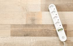 Extension cord on wooden floor, top view with space for text. Electrician`s equipment royalty free stock photography