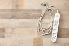 Extension cord on wooden floor, top view with space for text. Electrician`s equipment royalty free stock photo