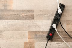Extension cord on wooden floor, top view with space for text. Electrician`s equipment royalty free stock images
