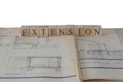 Extension written on wooden blocks on house extension building plans blueprints. With a white background stock images
