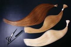 Extensiones del pelo de tres colores en un fondo oscuro con las tijeras y el peine Opinión superior de Copyspace imagen de archivo