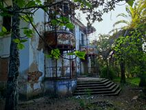 Exterior of abandoned house. Exterior of decaying abandoned  house overgrown with plants and trees Stock Image