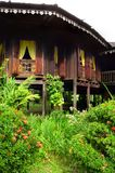 Exterior of antique Ethnic Malay house. A photograph showing the exterior details of a traditional wooden Malay ethnic house, with beautiful carved wood windows stock photo