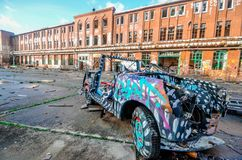 An exterior of an antique vintage roofless, roadster patterned car parked in front of an old school building in Berlin, Germany. stock images