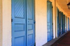 Exterior atractivo del edificio, con las puertas azules brillantes en pared amarilla del estuco Imagenes de archivo