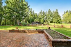 Exterior of Beautiful Secluded home. With Large brick paved Patio for Entertaining, a view of Guest Suite and detached Car Garage spaces. Northwest, USA Royalty Free Stock Images