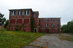 Exterior of boarded up and abandoned brick asylum hospital building with broken windows. Exterior of boarded up and abandoned historic brick asylum campus royalty free stock photos