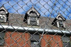 Exterior of boarded up and abandoned brick asylum hospital building with broken windows surrounded by chain link fence. Exterior of boarded up and abandoned royalty free stock image