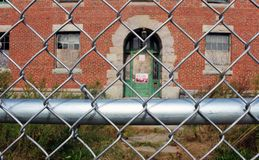 Exterior of boarded up and abandoned brick asylum hospital building with broken windows surrounded by chain link fence. Exterior of boarded up and abandoned Royalty Free Stock Photography