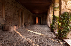 Exterior corridor bathed in sunlight. Door open at the end of the hallway lit by soft sunlight Royalty Free Stock Photography