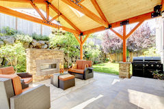Exterior covered patio with fireplace and furniture. Stock Photo