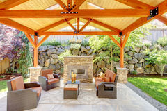 Exterior covered patio with fireplace and furniture. Wood ceiling with skylights Stock Image