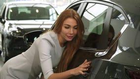 Exterior de examen de la mujer atractiva de un nuevo auto en la concesión de coche almacen de metraje de vídeo