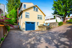 Exterior de la casa amarilla con la puerta del garaje y la calzada azules del asfalto Imagen de archivo libre de regalías