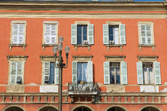 Exterior de la casa roja hermosa del estuco con las ventanas francesas tradicionales en Niza, Francia del obturador Foto de archivo libre de regalías