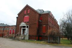 Exterior de subido para arriba y edificio abandonado del hospital del asilo del ladrillo con las ventanas quebradas Imagen de archivo libre de regalías