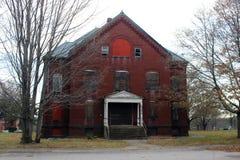 Exterior de subido para arriba y edificio abandonado del hospital del asilo del ladrillo con las ventanas quebradas Foto de archivo