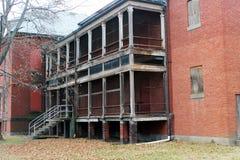 Exterior de subido para arriba y edificio abandonado del hospital del asilo del ladrillo con las ventanas quebradas Imagen de archivo