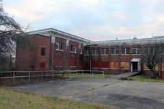 Exterior de subido para arriba y edificio abandonado del hospital del asilo del ladrillo con las ventanas quebradas Fotos de archivo