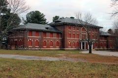 Exterior de subido para arriba y edificio abandonado del hospital del asilo del ladrillo con las ventanas quebradas Foto de archivo libre de regalías