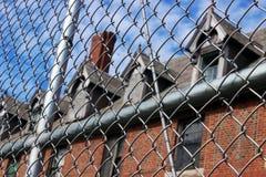 Exterior de subido para arriba y edificio abandonado del hospital del asilo del ladrillo con las ventanas quebradas rodeadas por  Imagen de archivo libre de regalías