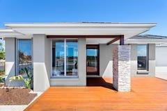 Exterior de una casa moderna con un piso de madera con el cielo azul Imagen de archivo libre de regalías