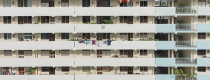 Exterior dense of HDB apartment complex in Singapore. Exterior dense of HDB housing flats with sun drying hanging clothes line in Singapore. Urban concept with Royalty Free Stock Photo