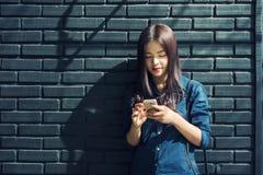 Exterior derecho contra la pared de ladrillo pintada, u de la mujer asiática joven Fotografía de archivo libre de regalías