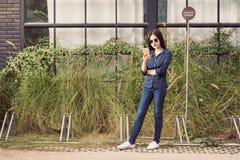 Exterior derecho de la mujer asiática joven usando su teléfono elegante Fotos de archivo libres de regalías