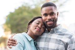 Exterior derecho de los pares africanos jovenes felices en un día soleado imágenes de archivo libres de regalías
