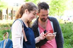 Exterior derecho de los pares alegres en parque urbano con los teléfonos móviles Imagenes de archivo