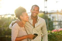 Exterior derecho de los pares felices con la mujer que sostiene el teléfono imágenes de archivo libres de regalías